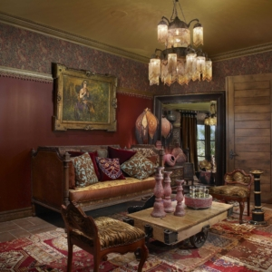 Living room with red walls, paisley, animal print and a wooden coffee table