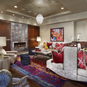 Living room with white walls, a tiled fireplace and abstract art